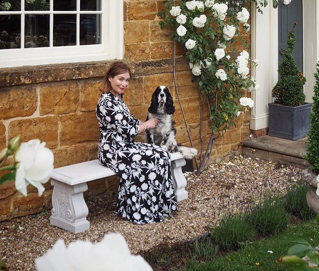 katy smith poses with her dog on the haddonstone scrolled bench