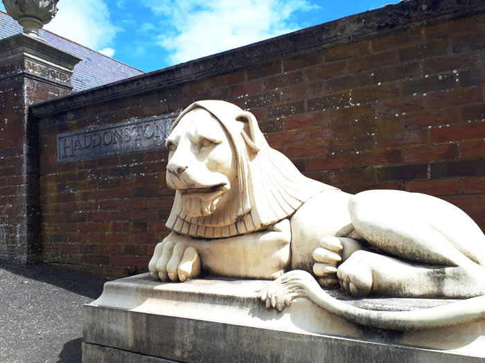 a large haddonstone cast stone lion at the entrance to the company's head office